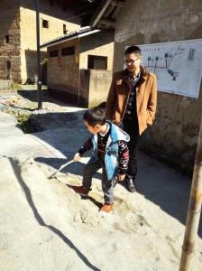 台灣醫生陳柏睿帶著孩子在土樓前玩耍。(新華社圖片)