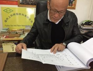 張傳來在福州的公司裡翻閱張氏族譜。