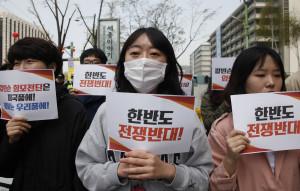 南韓首爾的美國駐韓大使館附近,南韓民眾手舉反戰標語參加集會。     (新華社 姚琪琳 攝)
