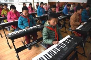 四川甘孜藏區全面推行免費教育政策,該地區的學生們在學習電子琴。 (新華社 薛玉斌 攝)
