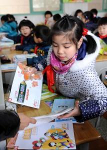 南京師範大學附屬小學二年級的學生在領取新學期的免費教科書和作業本。 (新華社 孫參 攝)
