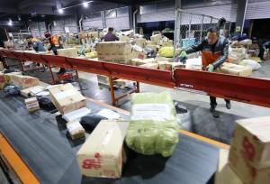 在山東省濰坊市一家快遞公司分揀中心,工作人員在分揀貨件。  (新華社 張馳 攝)