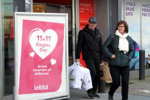 在挪威首都奧斯陸,兩名消費者從「雙十一」促銷廣告旁走過。 (新華社 梁有昶 攝)