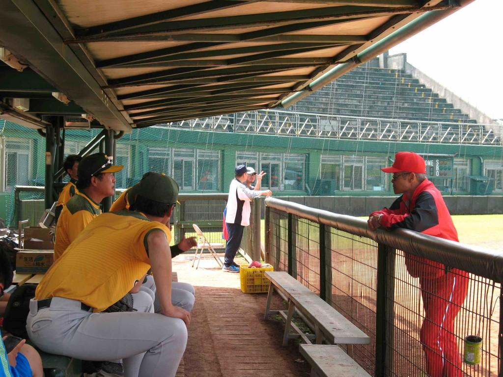 身穿紅色球衣的楊教練和江教練寒暄問暖