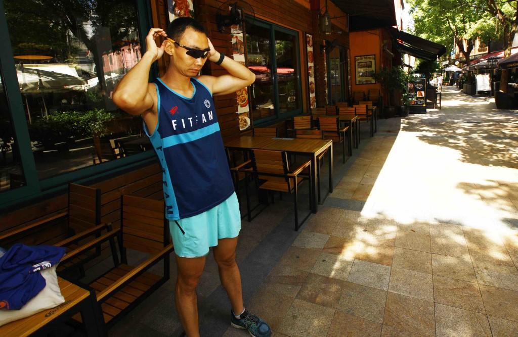 在上海虹梅路一處商業街樹蔭下,陪跑師孔斌在做跑前熱身運動。 (新華社 方喆 攝)
