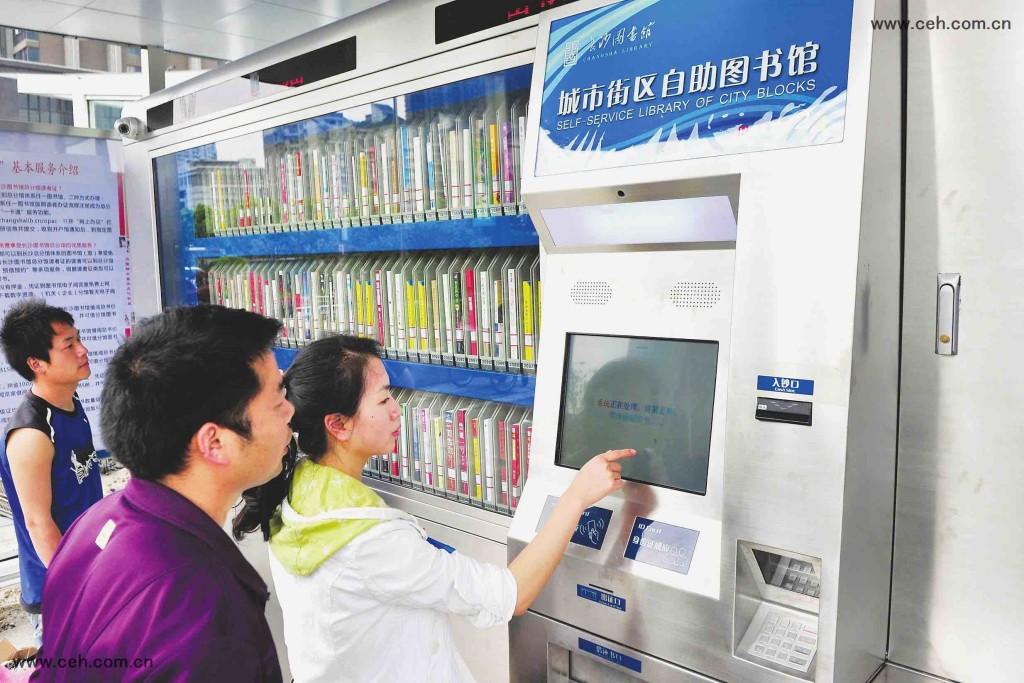 湖南省長沙市岳麓區步步高商業廣場前坪,市民在城市街區自助圖書館借書。