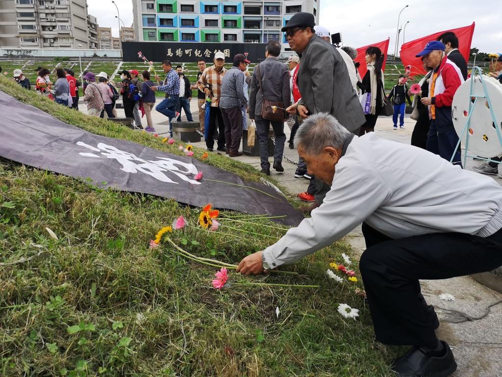 受難人與家屬向土丘獻花。