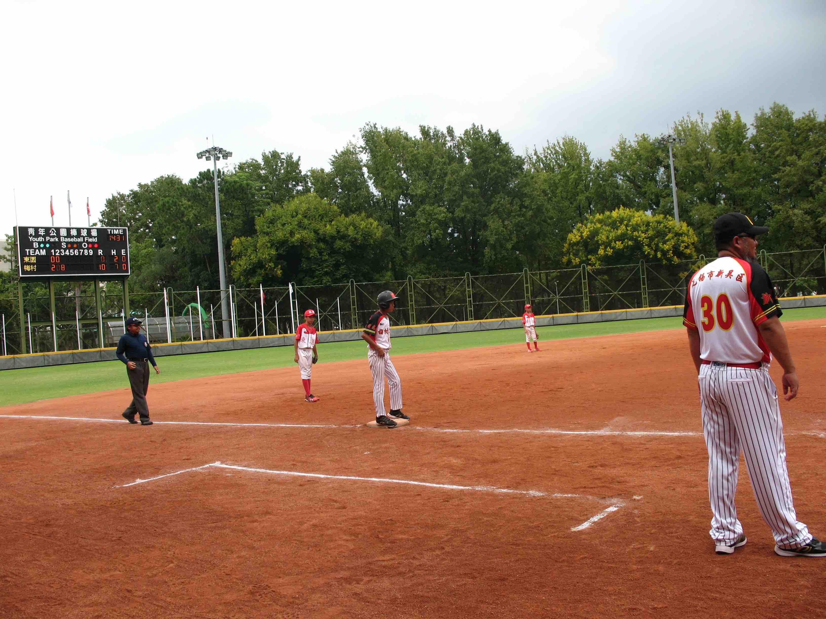 李偉教練站上三壘指導區給場上的無錫梅村實驗小學棒球隊小球員指導。